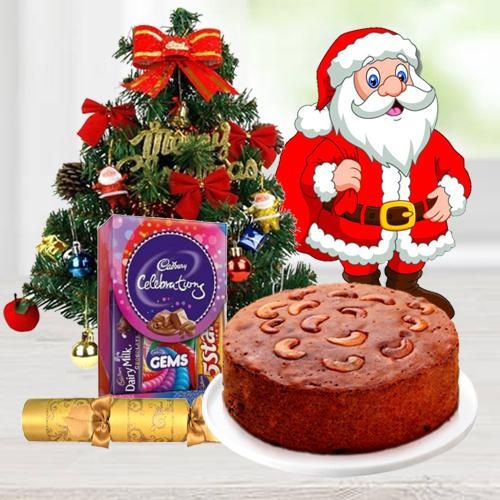 Christmas Fruit Cake 1 Lbs. with Christmas Tree 1 Ft. long artificial, Assorted Cadbury�s Chocolates for hanging ( 130 G.), Star and Bells for decoration, Santa Claus and  Handheld Ribbon Crackers for Christmas