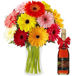 Shop Gerberas in a Glass Vase with a Bottle of Fruit Juice Online